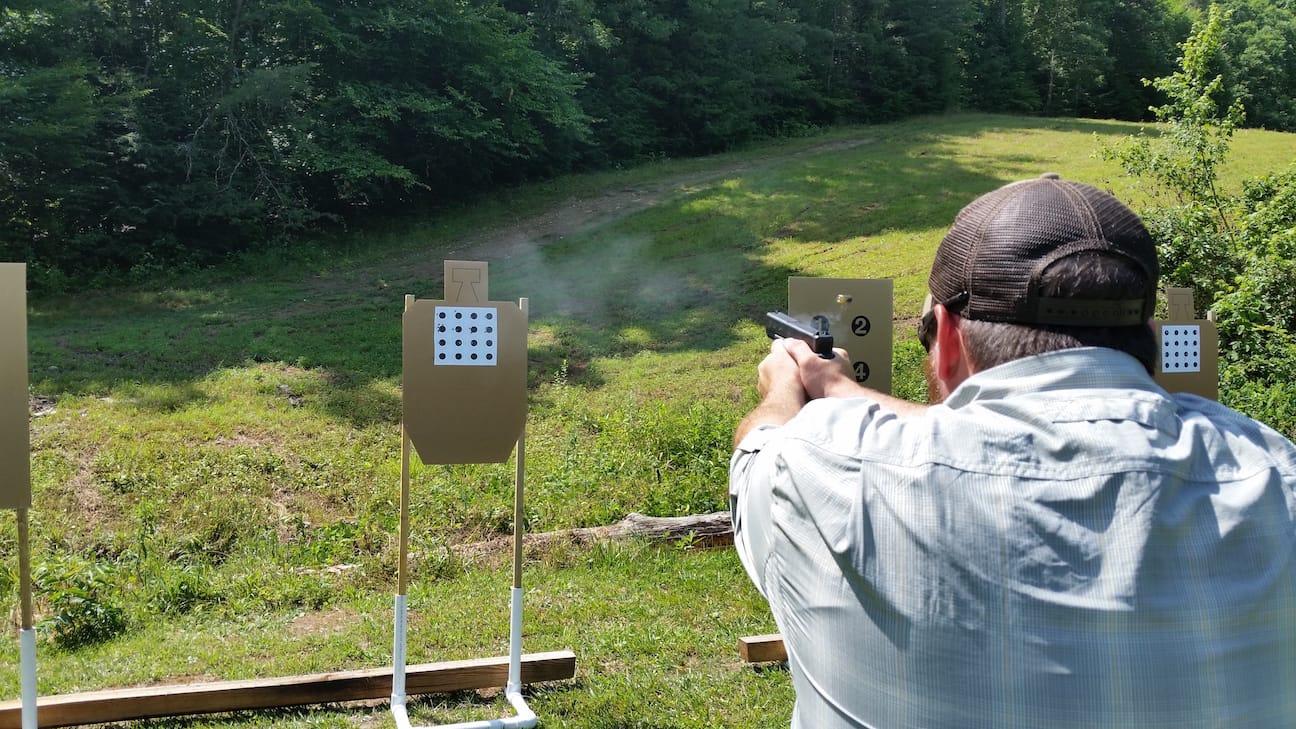 "A student hones marksmanship skills by shooting 1"" bullseyes"